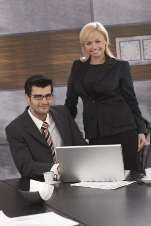Portrait of elegant businesspeople working together in meetingroom, smiling, looking at camera. photo