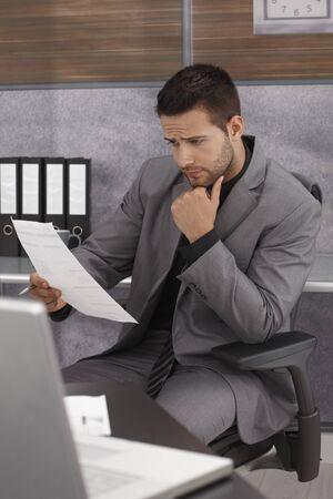 revisando documentos: Problemas de negocios sentado en el escritorio, mirando los papeles, con el ceño fruncido.