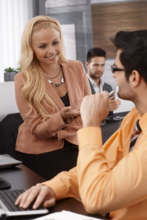 Young businesswoman sitting in office, talking to male colleague, smiling, gesturing. photo