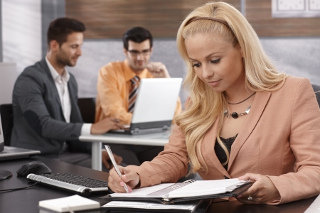 Blonde businesswoman working at desk in office. photo