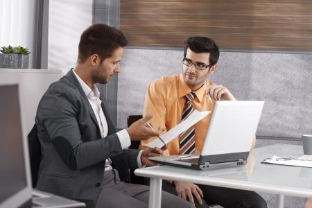 Businessmen sitting at desk, working together, using laptop computer.