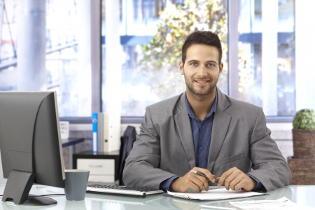 Portrait of happy handsome businessman sitting in bright office at desk, working.