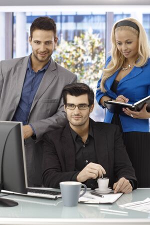 Elegant young businesspeople working in team, using computer, concentrating. photo