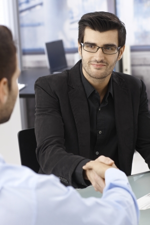 co workers: Businessmen sitting at desk, shaking hands, smiling. Stock Photo