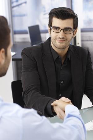 Businessmen sitting at desk, shaking hands, smiling. photo