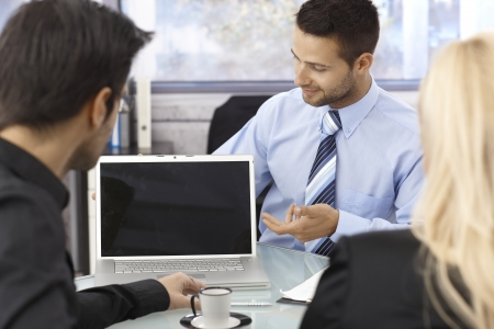 Businesspeople sitting at desk in office around open laptop with blank screen. Stock fotó