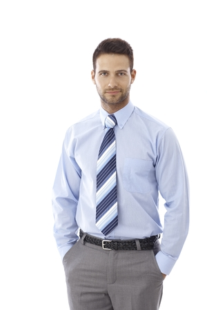 Portrait of handsome young businessman standing hands in pockets.