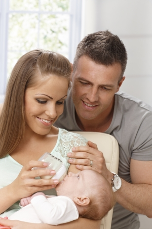 adoring: Young parents adoring baby. Mother holding in her arms and feeding her. Stock Photo
