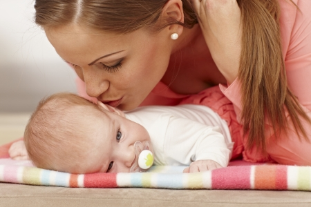 tenderly: Mother kissing lying baby tenderly.