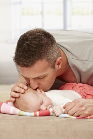tenderly: Father kissing sleeping baby tenderly.