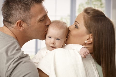be kissed: Young mother and father holding newborn baby, kissing head from two sides. Stock Photo