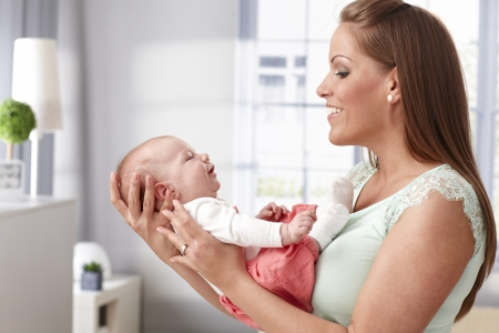 face of infant: Happy young mother holding newborn baby girl in arms, smiling to her. Stock Photo