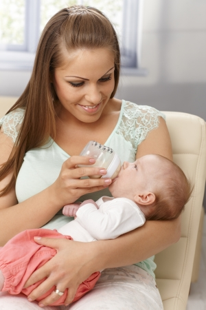 nursing bottle: Young mother feeding baby girl from feeding bottle, smiling, holding in arms.