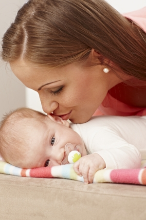 be kissed: Young mother kissing lying baby. Stock Photo