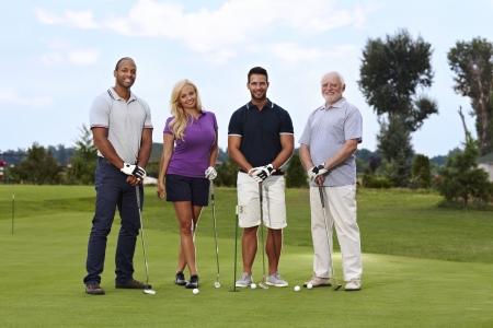 Groupe diversifié de golfeurs debout sur le vert, souriant, regardant la caméra.
