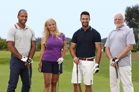 Happy group of golfers standing on the green, holding golf club.