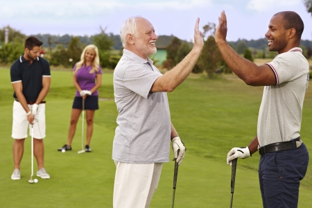 retirement age: Golf partners happy for good shot on the green. Stock Photo