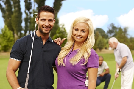 Attractive young couple standing and embracing at golf course. photo