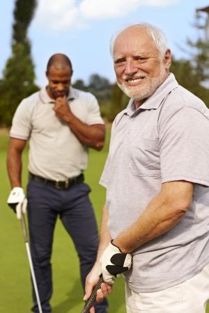Happy senior man golfing, smiling. photo