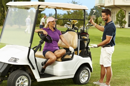 Happy male and female golfers talking on the fairway in golf cart. Stock Photo