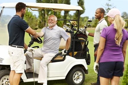 Golf partners greeting on the fairway around golf cart. photo