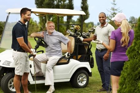 compa�erismo: Compa�erismo feliz listo para jugar al golf alrededor del carro de golf.