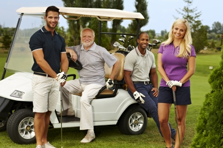 Happy team of golfers ready to play, standing and sitting around golf cart, smiling, looking at camera. photo