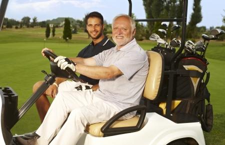 Gelukkig golfers zitten in golfkar, lachend, kijkend naar de camera. Stockfoto - 25483518