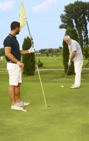 Young and old golfer playing together. photo