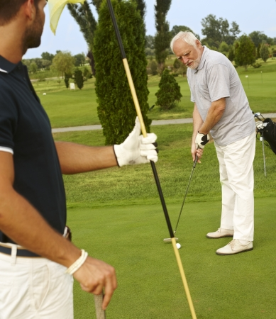 Senior male golfer holing, young man holding flag. photo