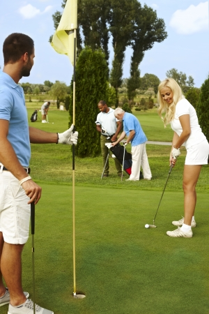 Pretty young female golfer holing, man holding flag. photo
