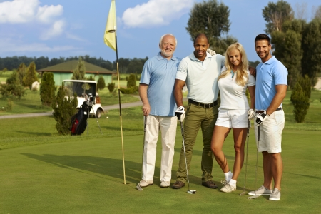 Happy people smiling, hugging on the golf course, ready to play, looking at camera. Stock Photo