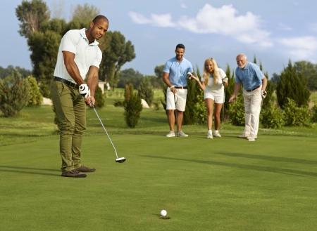 Männliche Golfspieler, der im Golfball auf dem Grün, Partner Jitter. Lizenzfreie Bilder