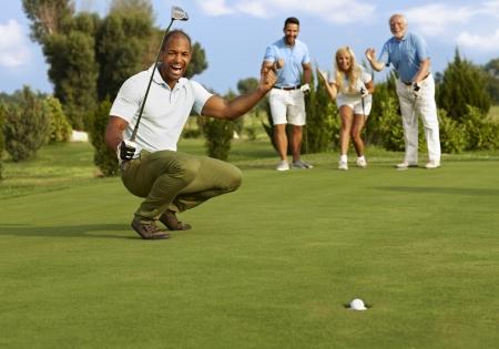 Homme golfeur et partenaires heureux pour putt réussi sur le vert.
