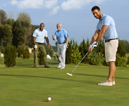 Young male golfer putting ball on green in the hole. Stock Photo