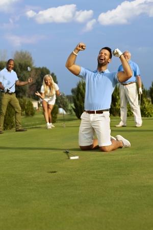 Junge männliche Golfer kniend glücklich Loch nach dem erfolgreichen Putt, schreiend mit Händen gefistet glücklich.
