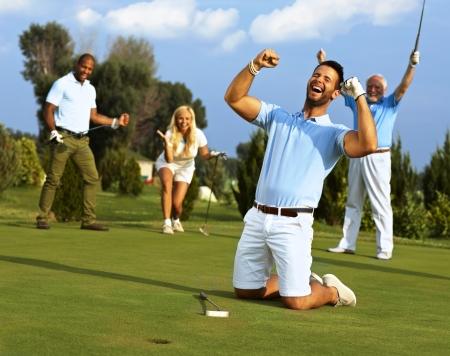 Gelukkig golfer geknield bij gat met opgeheven vuisten nadat hij in de golfbal naar de hole. Stockfoto