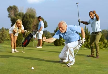 Golfeur senior heureux suivante balle de golf dans le trou après avoir mis.
