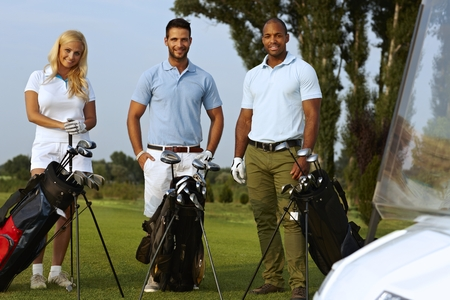 Happy golfers standing on golf fields with golfing kit, looking at camera, smiling. photo