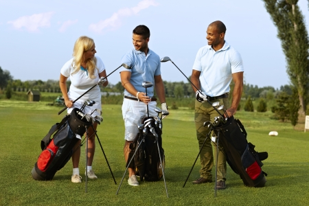 Happy partners standing on golf course, choosing golf club from golfing kit, starting game. Imagens