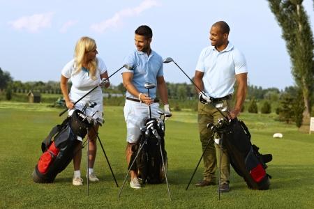 Partenaires heureux debout sur terrain de golf, club de golf qui choisissent de kit de golf, à partir match. Banque d'images