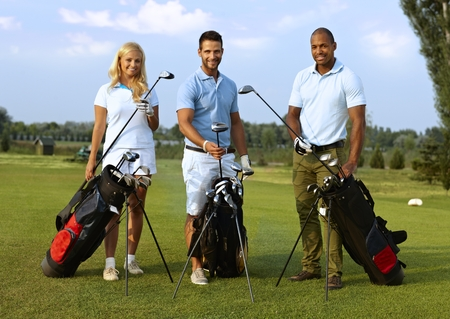Happy young golfers standing on golf course, smiling, looking at camera. photo