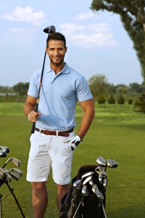 Portrait of handsome young golfer holding golf club, smiling, looking at camera.
