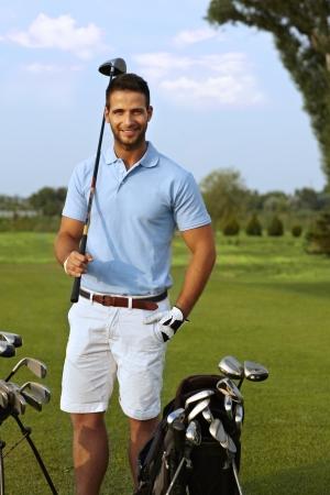Portrait de jeune golfeur beau tenue club de golf, souriant, regardant la caméra.