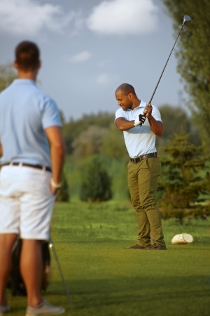 Ethnic male golfer teeing golf ball, swinging golf club. photo