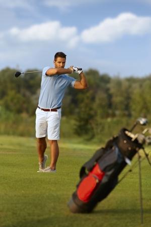 Young male golfer swinging golf club, following golf ball. photo