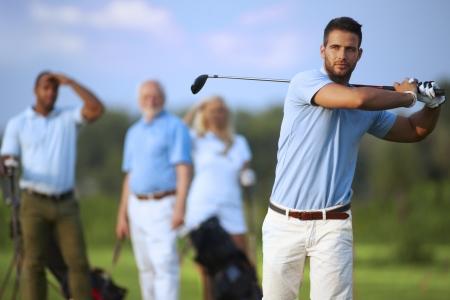 Handsome männlichen Golfspieler schwingen Golfschläger, nach Schuss in die Luft.
