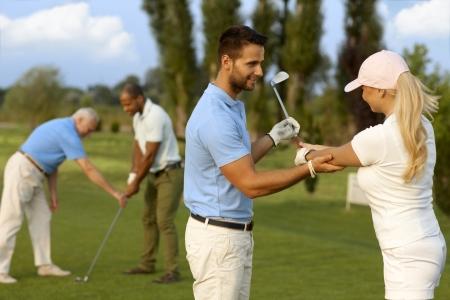 Žena golfista učení golf, samec instruktor pomáhá.