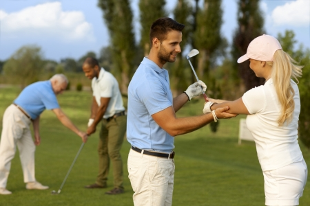 Female golfer learning golfing, male instructor helping. Standard-Bild