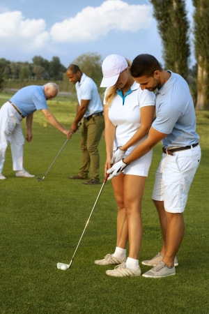 Male instructor teaching female golfer to hit the golf ball. Stok Fotoğraf